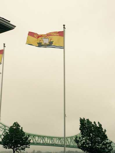 New Brunswick flag flying in front of the Van Horne bridge.